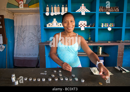 Cuban shopkeeper counting coins on the counter. Trinidad, Cuba. MODEL RELEASED SUBJECT - Stock Image