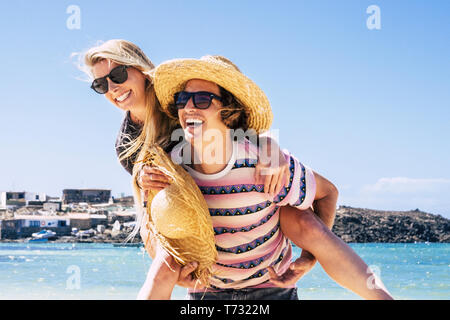 Young caucasian couple having fun at the beach in summer holiday vacation tourist people love travel and live together - happy lifestyle for man carry - Stock Image