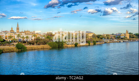 Guadalquivir river east bank from the Triana bridge, with the Giralda tower (left) and Golden Tower (right) among other landmarks. Seville, Spain. - Stock Image