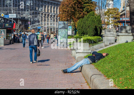 alcoholism and drug addiction in the city a drunk person is lying on the grass.Ukraine. Kiev 06.11.2018 - Stock Image