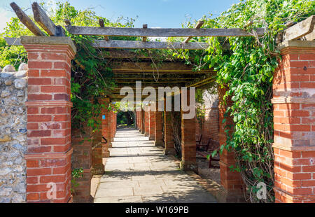 Red brick built traditional pergola in Connaught Gardens, Sidmouth, a pleasant popular south coast seaside town in Devon, south-west England - Stock Image