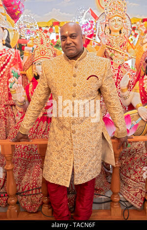 Posed portrait of a Hindu man in his fifties who assisted in morning services at his temple to celebrate his birthday. In Jamaica, Queens, New York. - Stock Image