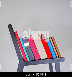 Colorful books on wooden chair near white stucco wall. - Stock Image
