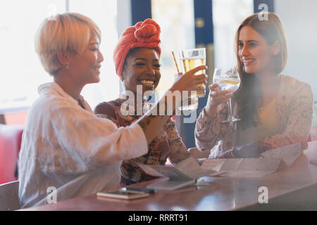 Happy, carefree young women friends toasting cocktail glasses in bar - Stock Image