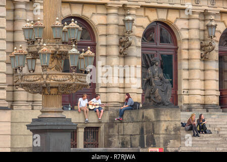 Young people talking, view of young people talking while sitting outside the Rudolfinum concert hall building in Prague, Czech Republic. - Stock Image