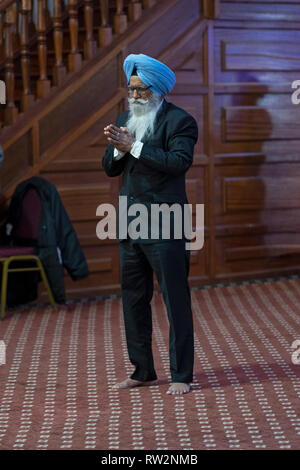 A devout Sikh man stands in prayer and meditation in a temple in South Richmond Hill, Queens, New York City. - Stock Image
