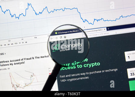 MONTREAL, CANADA - APRIL 26, 2019: Changelly cryptocurrency digital assets exchange logo and home page on a laptop screen under magnifying glass. - Stock Image