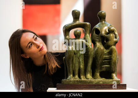 London, UK. 16 June 2017. A Christie's employee looks at the Henry Moore sculpture Family Group, 1946, estimate: - Stock Image