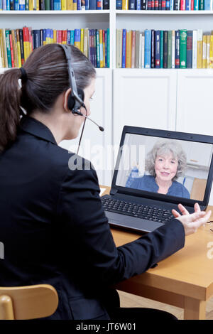 Female psychologist with headset in her office in front of her computer, talking to a senior woman during a live video call or chat, online counseling - Stock Image