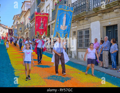 Annual Corpus Christi Parade on streets covered in flower petal design. Religioue banners. Ponte de Lima, Portugal, June 15, 2017 - Stock Image
