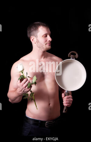 Man with a frying pan and a flower on a black background - Stock Image