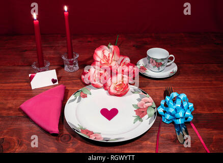 Floral pattern fine china dinnerware with matching plate, cup and saucer. bouquet of orange and white rpses, pink napkin, silverware, red candles and  - Stock Image