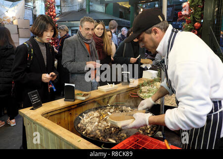 An Italian chef cooking hot wild mushroom spelt risotto at a Borough Market stall in South London England UK   KATHY DEWITT - Stock Image