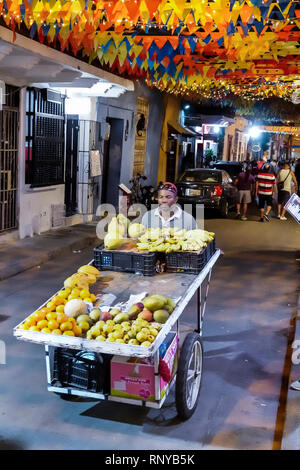 Cartagena Colombia Old Walled City Center centre Getsemani night nightlife Hispanic resident residents Calle San Andres colorful flags banners Black A - Stock Image