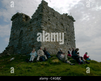 A group of walkers take a break at Rothley Castle (a folly) in Northumberland, and listen to the Northumbrian Pipes. - Stock Image
