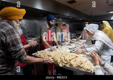 Women & men volunteers in a langar, a Sikh temple kitchen, prepare roti, a round thin bread. In South Richmond Hill, Queens, New York City. - Stock Image