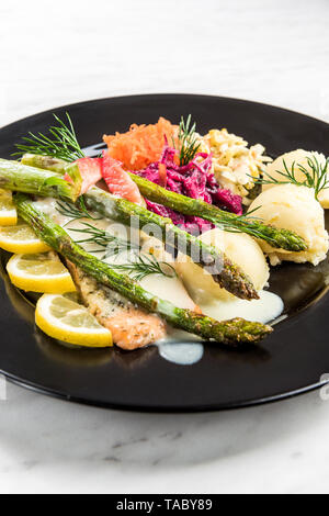 Grilled salmon with asparagus and potatoes, restaurant serving portion. - Stock Image