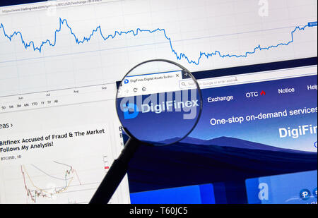 MONTREAL, CANADA - APRIL 26, 2019: DigiFinex cryptocurrency digital assets exchange logo and home page on a laptop screen under magnifying glass. - Stock Image