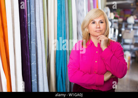 Portrait of  mature female standing among shelf in the curtains shop - Stock Image