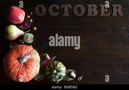 beautiful rustic fall flat lay with leaves, pumpkins, chestnuts and letters october on wooden background - Stock Image