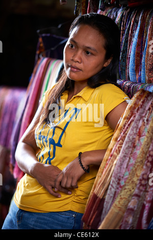 Young Balinese woman selling sarongs at Ubud Markets Bali Indonesia - Stock Image