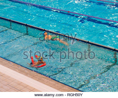 Poznan, Poland - January 26, 2019: Two boys swimming with sticks during swim lesson in a pool in the Termy Maltanskie. - Stock Image