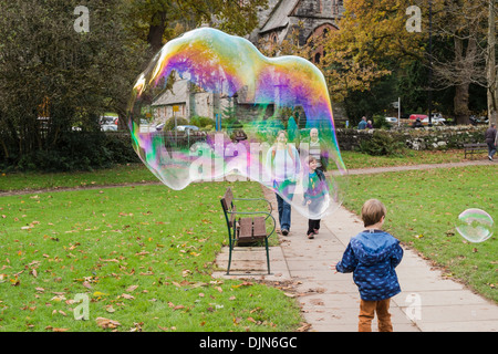 A young boy has fun with a giant soap bubble showing rainbow colours and people smiling in Betws-y-Coed, Conwy, North Wales, UK - Stock Image