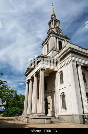 London, England, UK - June 1, 2019: Sun shines on the spire and portico of the Georgian All Saints Church in Poplar in London's East End. - Stock Image