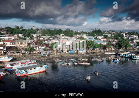 Wooden taxi boat ferry carries passengers across the river in Manado, Sulawesi, Indonesia - Stock Image