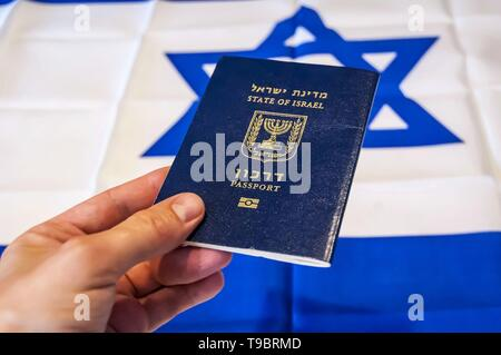 Hand holding the passport of the State of Israel, Israeli flag on the background. Israel citizenship concept, Israeli biometric 'darkon' passport - Stock Image