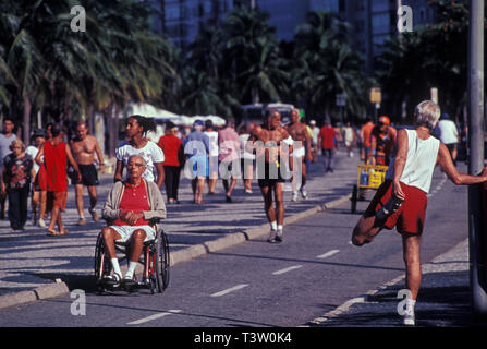Contrast - several healthy senior people exercise near a disabled wheelchair user elderly man cared by a young black woman at Copacabana beach sidewalk, Rio de Janeiro, Brazil. - Stock Image