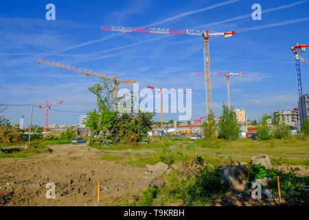 Multiple cranes in residential apartment  complex construction siteagainst blue sky with airplanes emission streaks, May 2019 Toulouse France - Stock Image