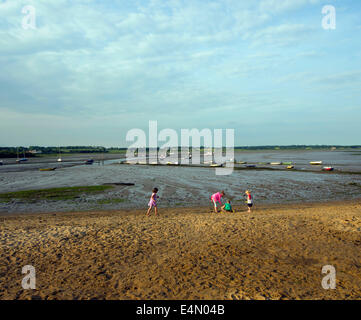 children playing on the narrow sandy beach by the side of the mudflats of The River Stour at Manningtree. - Stock Image
