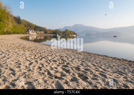 Luss, Loch Lomond, Scotland, UK. 22nd Apr, 2019. uk weather - a glorious still and hazy morning at Luss, Loch Lomond, overlooking the distinctive outline of Ben Lomond ahead of what is forecast to be a beautiful sunny day. Credit: Kay Roxby/Alamy Live News - Stock Image