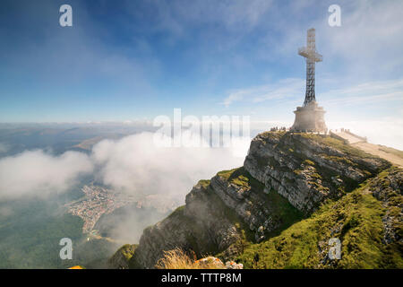 View of cross on mountain against sky - Stock Image