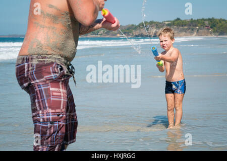 Family fun on the beach, water gun fight between toddler child and adult man - Stock Image