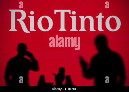 The Rio Tinto logo is seen on an LED screen in the background while a silhouetted person uses a smartphone in the foreground (Editorial use only) - Stock Image
