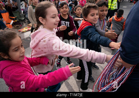 Volunteer hands out souvenir beads to kids on parade route during annual Washington's Birthday Celebration parade in downtown Laredo, Texas. - Stock Image