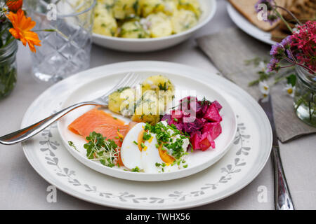 Scandinavian midsummer feast with potato salad, salmon and beetroot - Stock Image