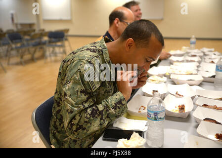 180829-N-BN978-002 GREAT LAKES, Ill (August 29, 2018) Training Support Center (TSC) staff member Lt. Dennis Barrett is busy judging entries submitted at the command's Rib Cook Off event Aug. 29. Nine TSC Sailors submitted their ribs in which Navy Military Training Instructor Engineman 1st Class Michael Newton was chosen winner. (U.S. Navy photo by Brian Walsh/Released) - Stock Image