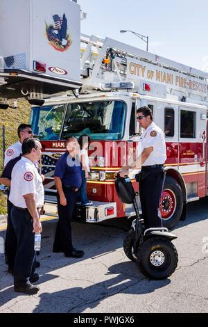 Miami Florida Little Havana Calle Ocho Eighth 8th Street Fire-Rescue fire truck ladder firefighter fireman man men girl Segway p - Stock Image