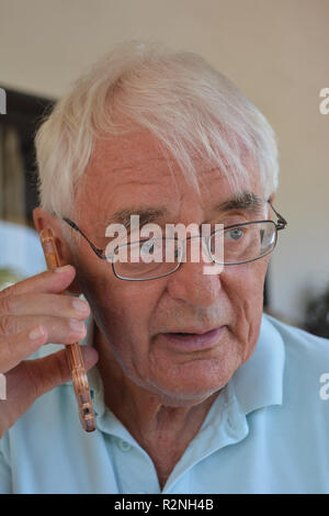 Senior man on a mobile phone, looking concerned - Stock Image