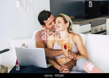 Cheerful and happy couple hugging and laughing at home lay down on the sofa - love and relationship concept with lifestyle healthy concept - technolog - Stock Image