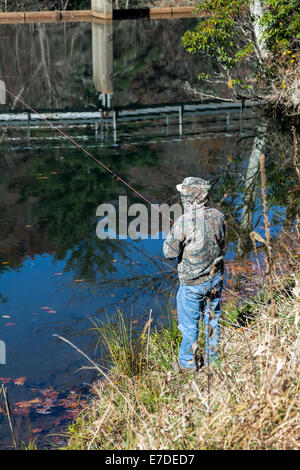 Fly fisherman casting on shore of Tuckasegee Lake and dam along scenic route NC 107 in mountains of SW North Carolina, - Stock Image