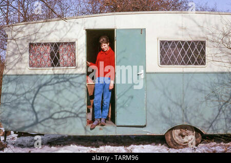 Archival 1960s just married young woman standing in doorway of dilapidated old caravan snow covered building site first marital home 60s England UK - Stock Image