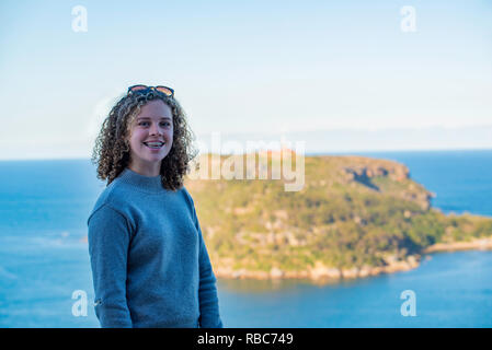 A young (16) white Australian girl with long blonde curly hair and braces gives a big smile at Sydney's West Head with Barrenjoey in the background. - Stock Image