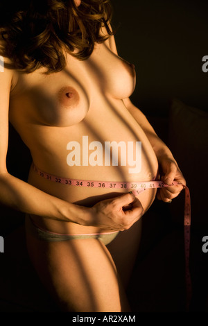Pregnant woman with measuring tape around her belly - Stock Image