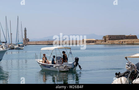 Chania, Crete, Greece. June 2019. The Old Venetian Harbour in Chania, people learning to control their hire boat - Stock Image