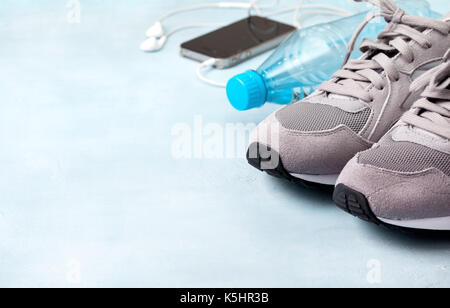 gray sneakers, bottle of water, smartphone with headphones on a blue background - Stock Image