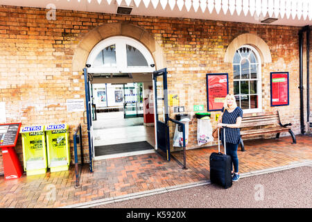 Woman with suitcase, woman traveling alone, woman traveler, traveling alone, solo traveler, female traveler, woman at train station, woman, alone, - Stock Image